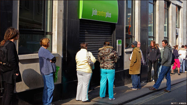 People wait outside a branch of Jobcentre in the UK