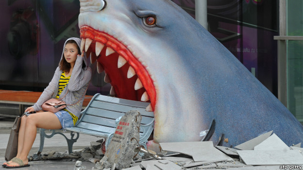 A tourist sits next to a large art display of a shark at a shopping mall in Bangkok.