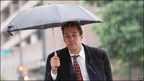 A man walking in the rain with an umbrella