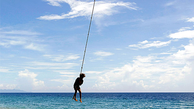 A girl swings on a rope attached to a palm tree on Bonegi beach.