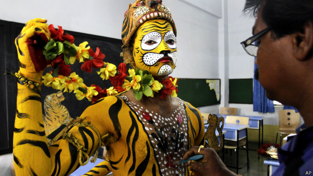 A dancer's body is painted to look like a yellow tiger before a performance.