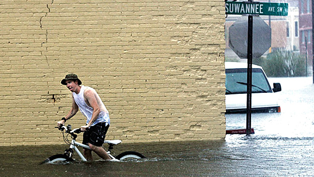 A man tries to cycle through flood water