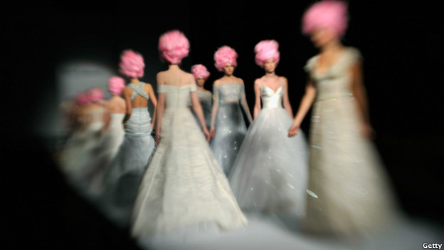 Models wearing white dresses and pink wigs on a catwalk.