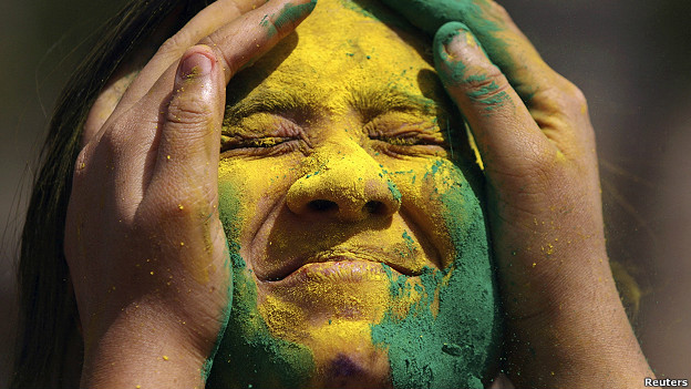 An Indian woman has coloured powder put on her face