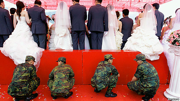 Soldiers crouch behind a platform as married couples pose for photos