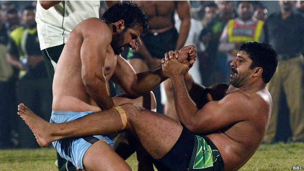 Kabaddi players grip each other