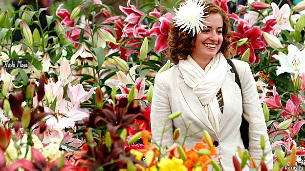 A woman looks at different coloured lilies in a garden