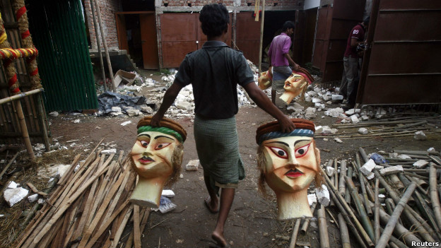 A man carries polystyrene heads to form part of a platform being built for the Durga Puja festival.