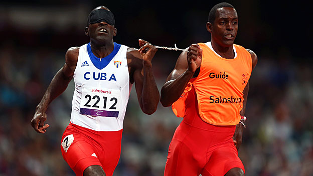 Yaseen Perez Gomez guides Arian Iznaga of Cuba around the track in the men's 200m, T11 race.