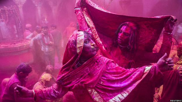 Men covered in pink powder during festival of Lath mar Holi in Northern India