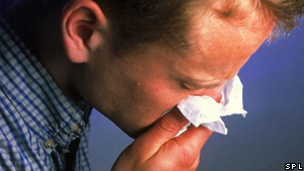 A man blowing his nose on a tissue