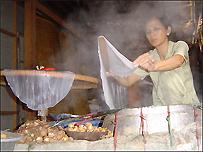 Một phụ nữ đang làm bánh cuốn