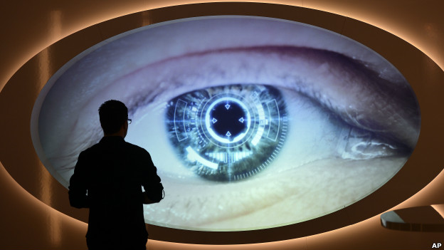 A man watches a screen that shows an eye being scanned at Germany's spy museum.