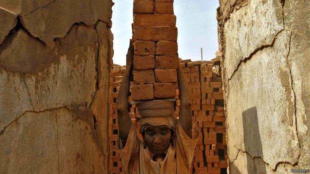 A woman carries bricks on her head in India